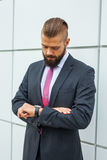 Giovane bussinessman nervoso che controlla tempo mentre aspettando una riunione immagine stock libera da diritti