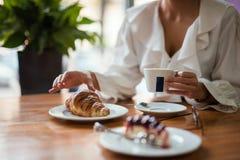 Giovane caffè bevente della donna elegante in caffè tradizionale, pasticceria, pasticceria immagini stock