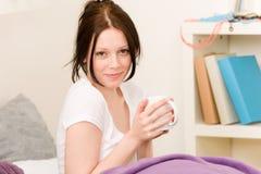 Giovane caffè della bevanda della ragazza dell'allievo in base Immagine Stock Libera da Diritti