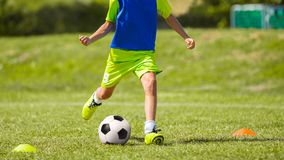 Giovane calciatore che dà dei calci alla palla sul passo di calcio Immagini Stock Libere da Diritti