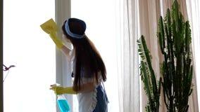 Giovane cameriera che pulisce una finestra stock footage