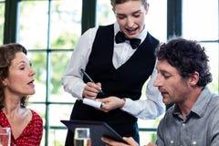 Giovane cameriera di bar che prende un ordine da una coppia Fotografie Stock Libere da Diritti