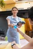 Giovane cameriera di bar professionista che prende carta mentre tenendo il cuscinetto del perno fotografia stock libera da diritti