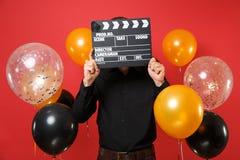 Giovane in camicia nera che tiene nascondersi coprendo fronte di ciac nero classico di produzione cinematografica sull'aria rossa fotografia stock