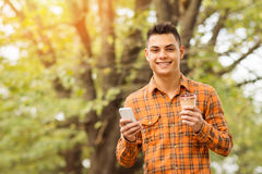 Giovane in camicia a quadretti arancio con lo Smart Phone ed il caffè in parco in autunno Immagine Stock