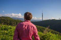 Giovane in camicia rosa dalla parte posteriore che gode di bella montagna vi Fotografia Stock Libera da Diritti