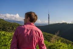 Giovane in camicia rosa dalla parte posteriore che gode di bella montagna vi Immagini Stock