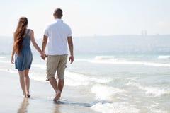 Giovane camminata delle coppie alla spiaggia Fotografia Stock