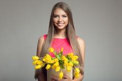 Giovane canestro felice della tenuta della donna con i tulipani gialli Backgr grigio immagine stock
