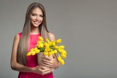 Giovane canestro felice della tenuta della donna con i tulipani gialli Backgr grigio immagine stock libera da diritti