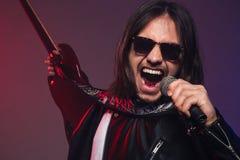 Giovane cantante brutale emozionante in occhiali da sole che canta e che tiene chitarra Fotografia Stock