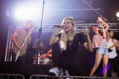 Giovane cantante femminile che esegue con i musicisti al night-club durante il festival di musica Fotografie Stock