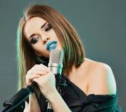 Giovane canto di modello sensuale in un microfono Donna di bellezza Fotografia Stock Libera da Diritti
