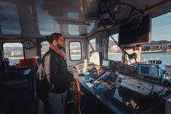 Giovane Capitan con la barba sta al timone e controlla la nave, vista dall'interno della cabina del ` s di capitano fotografie stock libere da diritti