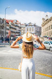 Giovane cappello della tenuta della donna del viaggiatore ed osservare in avanti la vista stupefacente della città Vocazione di e Fotografia Stock