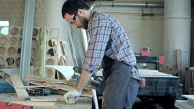 Giovane carpentiere che lavora con la macchina elettrica nell'officina Immagine Stock