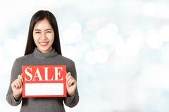 Giovane carta asiatica attraente dell'insegna di vendita della tenuta della donna che mostra per il prezzo da pagare che esamina  immagine stock libera da diritti