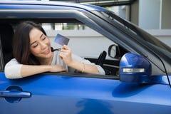 Giovane carta asiatica felice di pagamento della tenuta della donna o carta di credito ed usato per pagare benzina, alle stazioni fotografie stock libere da diritti
