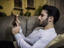 Giovane a casa che legge con il lettore del libro elettronico fotografia stock