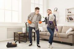 Giovane casa di pulizia delle coppie, divertendosi immagine stock