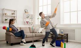 Giovane casa di pulizia delle coppie, giocante con la zazzera fotografie stock libere da diritti