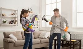Giovane casa di pulizia delle coppie, giocante con la zazzera fotografia stock libera da diritti