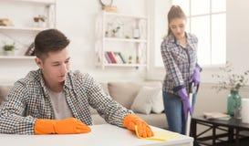 Giovane casa di pulizia delle coppie insieme fotografia stock