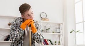 Giovane casa stanca di pulizia dell'uomo, spazzante immagine stock