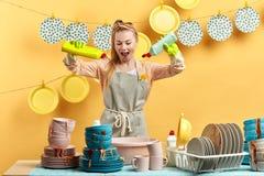 Giovane casalinga allegra che tiene due bottiglie con il liquido del pulitore immagini stock
