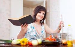 Giovane casalinga che cucina con il libro di cucina Immagini Stock