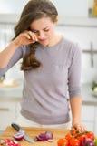 Giovane casalinga che grida mentre tagliando cipolla Immagine Stock