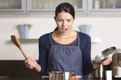 Giovane casalinga che ha una calamità nella cucina Fotografia Stock
