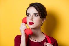 Giovane casalinga con il microtelefono rosso fotografia stock libera da diritti