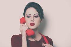 Giovane casalinga con il microtelefono rosso fotografie stock libere da diritti