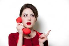 Giovane casalinga con il microtelefono rosso fotografia stock