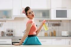 Giovane casalinga divertente con il detersivo immagine stock libera da diritti