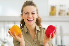 Giovane casalinga felice che tiene i peperoni dolci rossi e gialli Immagini Stock