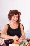 Giovane casalinga graziosa della donna che cucina con i bigodini Immagini Stock Libere da Diritti