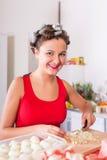 Giovane casalinga graziosa della donna che cucina con i bigodini su capelli Fotografia Stock Libera da Diritti