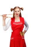 Giovane casalinga in grembiule rosso luminoso con la tenuta divertente delle code di cavallo fotografie stock libere da diritti