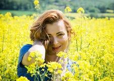 Giovane castana adorabile nel giacimento del seme di ravizzone Immagine Stock
