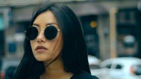 Giovane castana asiatico di fascino in occhiali da sole video d archivio