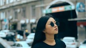 Giovane castana asiatico sexy nel sunglasse cammina intorno alla via video d archivio