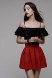 Giovane castana caldo in gonna rossa e blusa nera fotografia stock libera da diritti