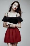 Giovane castana caldo in gonna rossa e blusa nera immagini stock libere da diritti