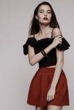 Giovane castana caldo in gonna rossa e blusa nera immagine stock