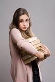 Giovane castana con il grande mucchio dei libri. Immagine Stock