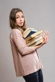 Giovane castana con il grande mucchio dei libri. Fotografia Stock