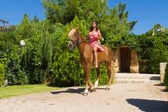 Giovane castana con il vestito rosso che guida il suo marrone Fotografia Stock