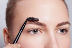 Giovane castana con trucco della donna dei capelli di scarsità cosmetico della ragazza Fotografie Stock Libere da Diritti